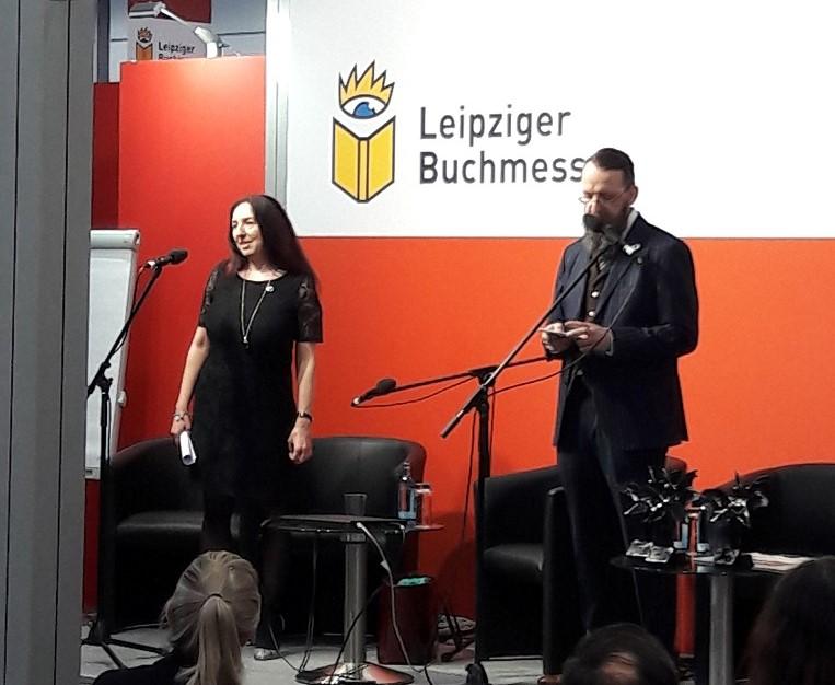 """Eine Frau und ein Mann an Mikrofonen, dahinter der Schriftzug """"Leipziger Buchmesse"""""""