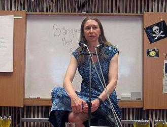 Foto von Frau auf Tisch sitzend vor Mirkofonen