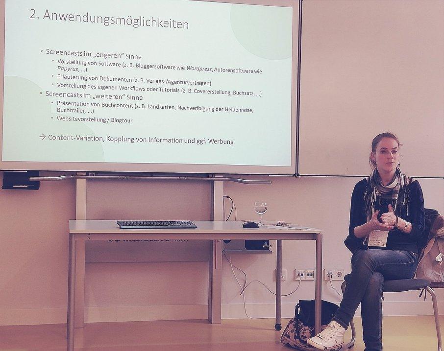 Frau sitzt vor PowerPoint-Präsentation über Anwendungsmöglichkeiten von Screencasts, z. B. Vorstellung von Software, Vorstellung des eigenen Workflows oder Präsentation von Buchcontent.