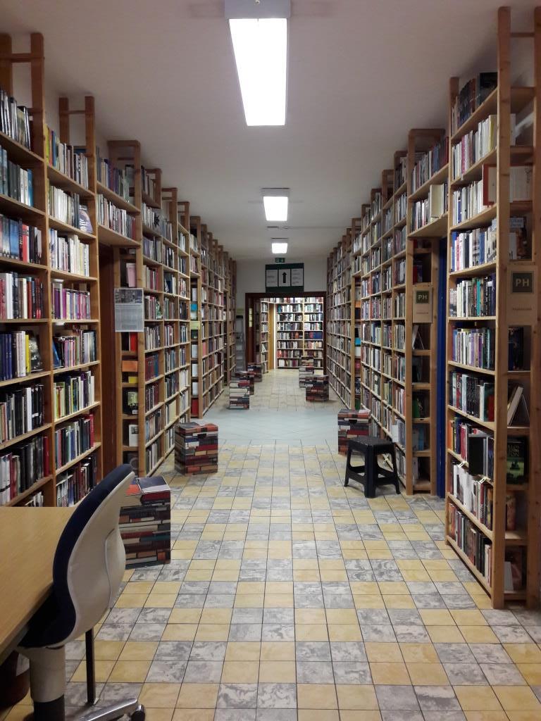 Bibliotheksgang mit vielen Regalen und Sitzhockern