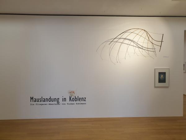 """Wand mit Aufschrift """"Mauslandung in Koblenz. Die Fliegerei-Abenteuer von Torsten Kuhlmann"""" mit Flügelgebilde"""